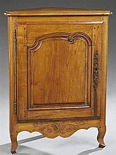 French Provincial Louis XV Style Carved Cherry Corner Cupboard, 20th c., the stepped edge triangular top over a raised panel cupboar...