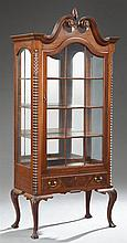 American Chippendale Style Carved Mahogany Display Cabinet, 20th c., the broken arch top centered by a flame finial over an arched m...