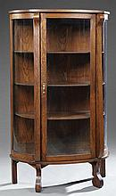 American Carved Oak Curved Glass Curio Cabinet, early 20th c., the bowfront top over a central curved glass door flanked by curved p...