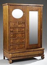 American Classical Carved Quarter Sawn Oak Wardrobe, c. 1900, the rectangular top over a mirrored door right, flanked left by a wide...