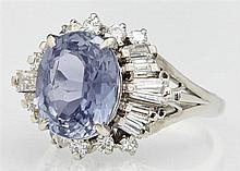 Lady's Platinum Dinner Ring, with a 4.35 carat oval blue sapphire atop a border of round and baguette diamonds, on a pierced sided b..