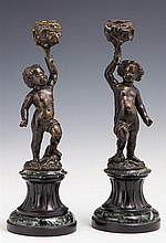 Pair of Patinated Bronze and Marble Figural Candlesticks, 19th c., of putti upholding relief decorated candle cups, on sloping verde...