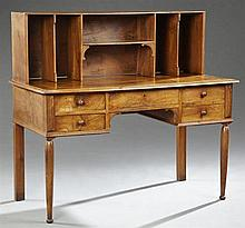 French Louis Philippe Carved Walnut Desk, 19th c., the rectangular back fitted with cubby holes and shelves, on a base with a steppe...