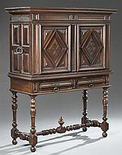 French Louis XIII Style Carved Walnut Cabinet on Stand, 19th c., the dentillated stepped crown over two raised panel cupboard doors...
