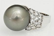 Lady's 14K White Gold Dinner Ring, with a 15 mm silver South Seas pearl, each side of the band topped by 12 round diamonds, total di...