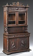 French Henri II Style Carved Oak Buffet a Deux Corps, late 19th c., the broken arch crest over two glazed doors flanked by barley tw...