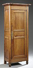French Empire Carved Cherry Bonnetiere, mid 19th c., the cookie corner crown over a single door with a long brass escutcheon flanked...