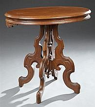 American Victorian Carved Walnut Center Table, late 19th c., the oval top over a wide reeded skirt on a quadripartite base with serp...