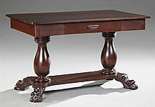 American Classical Revival Carved Mahogany Paw Foot Library Table, c. 1910, the rectangular top over a frieze drawer, on double balu...