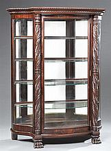 American Empire Carved Mahogany Serpentine Glass Curio Cabinet, 20th c., the gadrooned break front top over a bowed glazed door open...