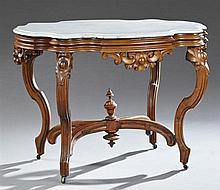 American Rococo Revival Carved Walnut Turtle Marble Top Center Table, 19th c., the serpentine figured white marble over a wide skirt...