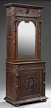 French Henri II Style Carved Oak Buffet a Deux Corps, 19th c., the carved crown above a mirrored door flanked by fruit carved stiles...