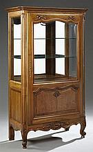 French Louis XV Style Carved Cherry Display Cabinet, 20th c., the stepped crown over a wide beveled glazed door with a lower fielded...