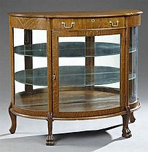 American Victorian Carved Golden Oak Curved Glass Display Cabinet, c. 1900, the serpentine demilune top over a bowed drawer over a c...