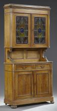 French Carved Walnut Buffet a Deux Corps, 19th c., the stepped canted corner crown over double doors with leaded stained glass panel...