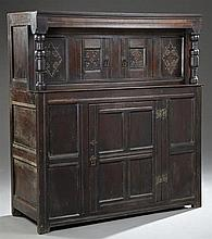 Jacobean Style Carved Oak Court Cupboard, 19th c., the stepped crown over two cupboard doors flanked by turned supports, on a base w...