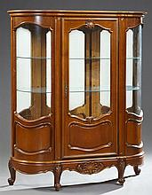 Louis XV Style Carved Cherry Curved Glass Curio Cabinet, 20th c., the stepped oval crown over a center door with a glazed upper pane...