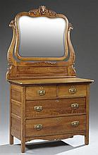 American Arts and Crafts Carved Oak Chest, late 19th c., the serpentine mirror over a bowed top above two frieze drawers, over two l...