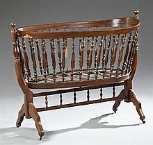 Late Victorian Turned Mahogany Baby Cradle, late 19th c., the oval spindle sided cradle within ring turned supports, on splayed serp...