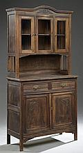 Continental Art Nouveau Carved Pine Buffet a Deux Corps, late 19th c., the stepped arched crown above a central bowed cupboard door...
