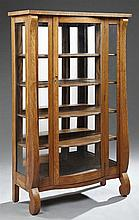 American Arts and Crafts Carved Oak Curved Glass Curio Cabinet, early 20th c., the rectangular top over a central curved glass door...