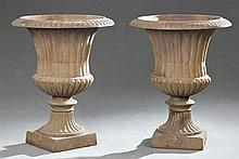 Pair of Campana Style Cast Iron Garden Urns, 20th c., the everted petal edge rim over a tapered body, on a tapered fluted socle to a...