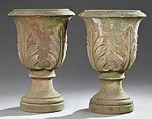 Pair of Large Continental Style Cast Iron Footed Campana Form Garden Urns, 20th c., the everted rim over leaf decorated sides on cir...