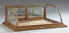 American Carved Oak Curved Glass Counter Display Case, late 19th c., the rectangular glass top to a curved glass front flanked by gl...