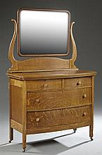 American Arts and Crafts Oak Dresser, c.1900, the serpentine shaped wide beveled mirror on a base with a bowed top, above two frieze...