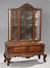 German Highly Carved Oak Vitrine, c. 1920, the arched crest with a central relief carved floral basket, over a glazed beveled door,...