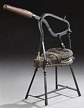 Leather Bellows, 19th c., labeled Foucheraud-Robichon, with a mahogany pump handle, on an iron stand, on spayed legs joined by recta...