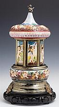 Reuge Capodimonte Music Box Carousel, 20th c., decorated with relief figures of putti, the doors opening to reveal cigarette bins, o...