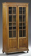 French Carved Poplar Bookcase, early 20th c., the stepped crown over double mullioned glazed doors with lower incised panels on a st...