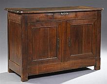 French Provincial Carved Walnut Sideboard, 19th c., the rounded corner top over two frieze drawers above double cupboard doors, on b...