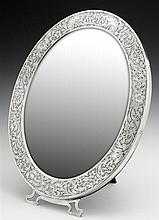 Unusual Sterling Easel Dressing Mirror, c. 1900, #1851, the wide frame with relief floral and scrolled decoration around an oval bev...
