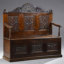 French Provincial Carved Chestnut Settle, 19th c., possibly Brittany, the back with an arched spindle back flanked by leaf carving,...