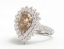 Lady's 18K White Gold Dinner Ring, with a 2.04 carat pear shaped fancy dark orangey brown diamond atop two concentric graduated rows..