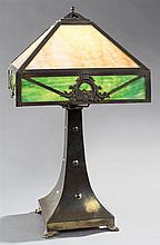 American Arts and Crafts Slag Glass Brass Lamp, c. 1910, the square shade with caramel and green glass panels with horseshoe and scr...