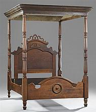 American Late Victorian Carved Walnut Tester Bed, c. 1890, the arched headboard with a pierced crest within turned posts, to an arch...