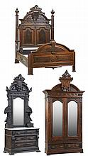 An American Renaissance Carved and Burl Walnut Bedroom Suite, c. 1870, consisting of a bed, dresser and armoire; the bed with an arc...
