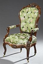 Victorian Carved Walnut Parlor Armchair, c. 1880, the fruit, nut and leaf carved crest over a tufted shield back, above upholstered...