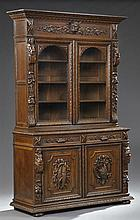 Jacobean Style Highly Carved Oak Buffet a Deux Corps, c. 1880, the upper section with a stepped ogee crown over a large lion's head...