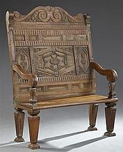 French Provincial Carved Oak Louis XVI Style Settee, early 19th c., the arched high back carved with musical instruments and floral...