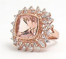 Lady's 14K Rose Gold Dinner Ring, with a cushion cut 8.65 carat morganite, atop a pierced frame of round diamonds and an outer row o..