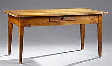 French Provincial Carved Cherry Farmhouse Table, 19th c., the rounded top over a wide skirt with a central frieze drawer, on square...