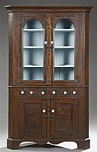 American Gilt and Faux Bois Carved Pine Two Part Corner Cabinet, 19th c., the ogee crown over double arched glazed doors, on a base...