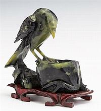 Oriental Carved Jadeite Bird, 20th c., on a custom carved hardwood stand, Figure- H.- 4 5/8 in., W.- 4 3/4 in.