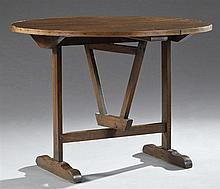 French Provincial Carved Pine Wine Tasting Table, 19th c., the folding circular top on a trestle base joined by a rectangular stretc...