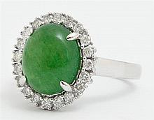Lady's 14K White Gold Dinner Ring, with an oval 4.89 cabochon jade stone, atop a border of round diamonds, total diamond wt.- .57 ct..