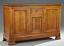 French Louis Philippe Style Carved Cherry Sideboard, 20th c., the canted corner rectangular top above a central drawer over a cupboa...